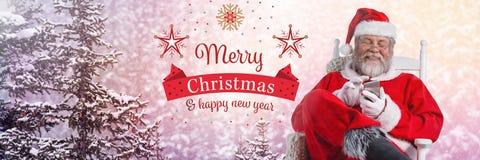 Texto y Santa Claus de la Feliz Año Nuevo de la Feliz Navidad en invierno con el teléfono Foto de archivo libre de regalías