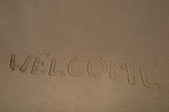 Texto y x22; welcome& x22; en el verano de la arena de la playa fotos de archivo