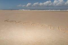 Texto y x22; welcome& x22; en la arena de la playa con las olas oceánicas en fondo Imagen de archivo libre de regalías