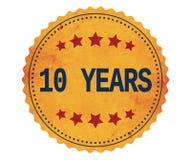 Texto 10-YEARS, en sello de la etiqueta engomada del amarillo del vintage Imagen de archivo