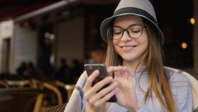 Textos de sorriso da menina no telefone no café vídeos de arquivo