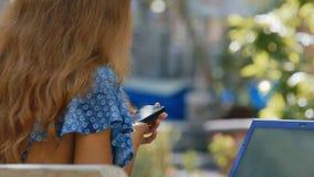 Textos rubios de la muchacha en Smartphone en la opinión del cierre de la parte trasera del parque almacen de video