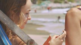 Textos rubios de la muchacha en teléfono en la playa por la resaca de la onda metrajes