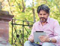 Textoter au collègue Homme adulte occasionnel tenant le comprimé numérique Images stock