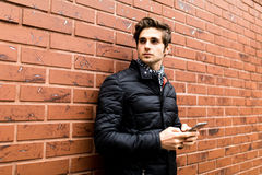Textoter au jeune homme beau d'amie dans la tenue de détente futée tenant le téléphone portable tout en se penchant sur le mur de Photo stock