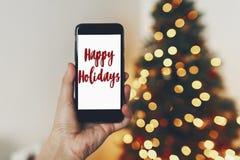 Textotez bonnes fêtes, des salutations de saisons sur l'écran de téléphone sur le backgr Photographie stock