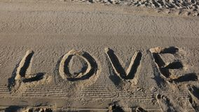 Textotez l'AMOUR dans le sable de la plage Photo libre de droits