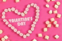 Textotez le jour du ` s de valentine dans la forme de coeur des bonbons concept d'amour sur le fond rose Images stock
