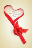 Textotez le jour et le ruban de valentines heureux formant un coeur Image stock