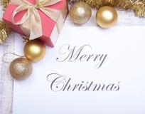 Textotez le Joyeux Noël sur le papier avec beaucoup de boules Photos stock