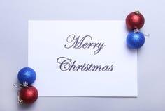Textotez le Joyeux Noël sur le papier avec beaucoup de boules Image libre de droits