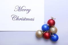 Textotez le Joyeux Noël sur le papier avec beaucoup de boules Image stock