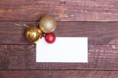 Textotez le Joyeux Noël sur le papier avec des boules au-dessus de fond en bois Photo stock