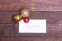 Textotez le Joyeux Noël sur le papier avec des boules au-dessus de fond en bois Photographie stock libre de droits