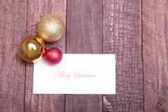 Textotez le Joyeux Noël sur le papier avec beaucoup de boules Photos libres de droits
