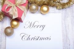 Textotez le Joyeux Noël sur le papier avec beaucoup de boules Photo libre de droits