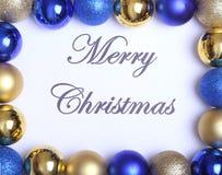 Textotez le Joyeux Noël sur le papier avec beaucoup de boules Photo stock