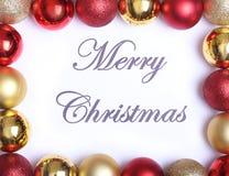 Textotez le Joyeux Noël sur le papier avec beaucoup de boules Photographie stock libre de droits
