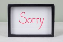 Textotez le mot DÉSOLÉ, cadre noir, sur la table blanche Images libres de droits