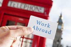 Textotez le travail à l'étranger dans une enseigne avec Big Ben dans le backgrou photographie stock libre de droits