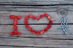Textotez les clous d'amour d'I faits à partir de la fraise sur le fond en bois Photographie stock