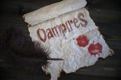 Textotez les vampires et les baisses de sang sur le papier de vintage avec le vieux stylo sur le bureau en bois Photo libre de droits