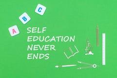 Textsjälvutbildning avslutar aldrig, från ovannämnda träminituresskolatillförsel och abc-bokstäver på grön bakgrund Royaltyfri Foto