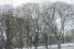 Textur av bokehdroppar på exponeringsglas framme av stads- parkerar landskap fotografering för bildbyråer