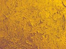 Textur av den gammala väggen med en sprucken guld- målarfärg. Fotografering för Bildbyråer