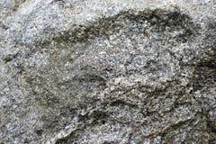 Textur av den gråa gamla hårda stenen med sprickor, bulor och modeller royaltyfria foton