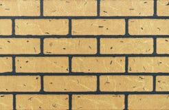 Textur av den gula tegelstenväggen för bakgrund arkivfoto