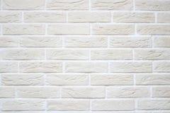 Textur av den ljus beiga skrapade lättnadstegelstenväggen med vitsömmar och rektangulära tegelstenar från dekorativ murbruk fotografering för bildbyråer