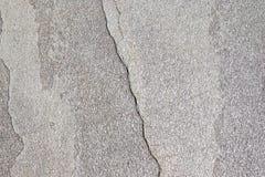 Textur av den naturliga stenen med en spricka Bakgrund av den naturliga stenen marmorerar grå färger med en splittring Grov textu royaltyfria bilder