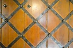 Textur av den robusa tränaturliga tjocka dörren för den gamla forntida medeltida antikviteten med nitar och spikar modeller, och  royaltyfria bilder