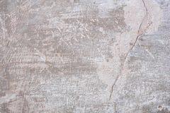Textur av en betongvägg med sprickor och skrapor som kan användas som en bakgrund arkivbilder