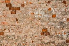 Textur av en gammal vägg av en forntida byggnad med ett förstört murbruklager och knäckte röda tegelstenar Arkivfoto