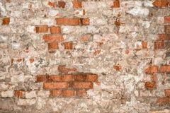 Textur av en gammal vägg av en forntida byggnad med ett förstört murbruklager och knäckte röda tegelstenar Arkivbild