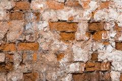 Textur av en gammal vägg av en forntida byggnad med ett förstört murbruklager och knäckte röda tegelstenar, abstrakt bakgrund Arkivbilder