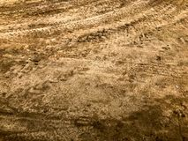 Textur av en smutsig dålig grusväggrusväg med pölar och lerauttorkninggyttja med sprickor och brunst Av-väg grönska för abstrakti royaltyfria foton