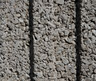 Textur av en vägg av små små gråa stenar med två skrattgropar i mitt arkivfoton