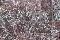 Textur av en vägg som göras av fyrkantiga röda marmortegelplattor Arkivbilder