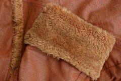 Textur av ett tyg som göras av bruna muffar med päls och läder Arkivfoto