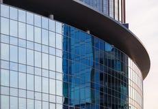 Textur av fasaden av glass byggnad av rund form med reflexionshimlen i den Royaltyfri Foto