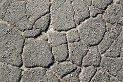 Textur av gammal sprucken asfalt i dagen II arkivbild