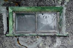 Textur av grå dekorativ murbruk med en stor spricka och ett fönster arkivfoto