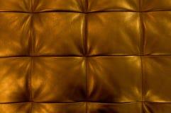 Textur av guld- bakgrund för stoppninglädermodell Arkivfoton
