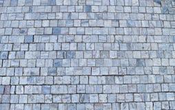 Textur av kubikstenstenläggningen på gatan Arkivbild