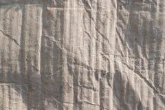 Textur av ljus bleknad beige papp i solljus och med skuggor, abstrakt tappningbakgrund Arkivbild