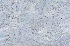 Textur av målad murbruk av den buse utföra i relief väggen av den yttre källaren av byggnad, blå bakgrund Arkivfoton