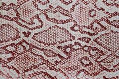 Textur av närbilden för äktt läder som utföra i relief under huden en reptil, med modemodellen och matteyttersida claret Royaltyfria Bilder